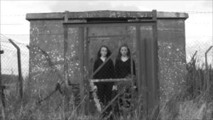 Black and white image of a pair of twins between a gate and a concrete bunker